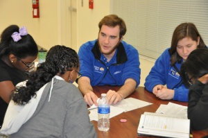 United Way AmeriCorps Member Zach Thorne tutoring students, including 11th grader Guissa Tera (left).